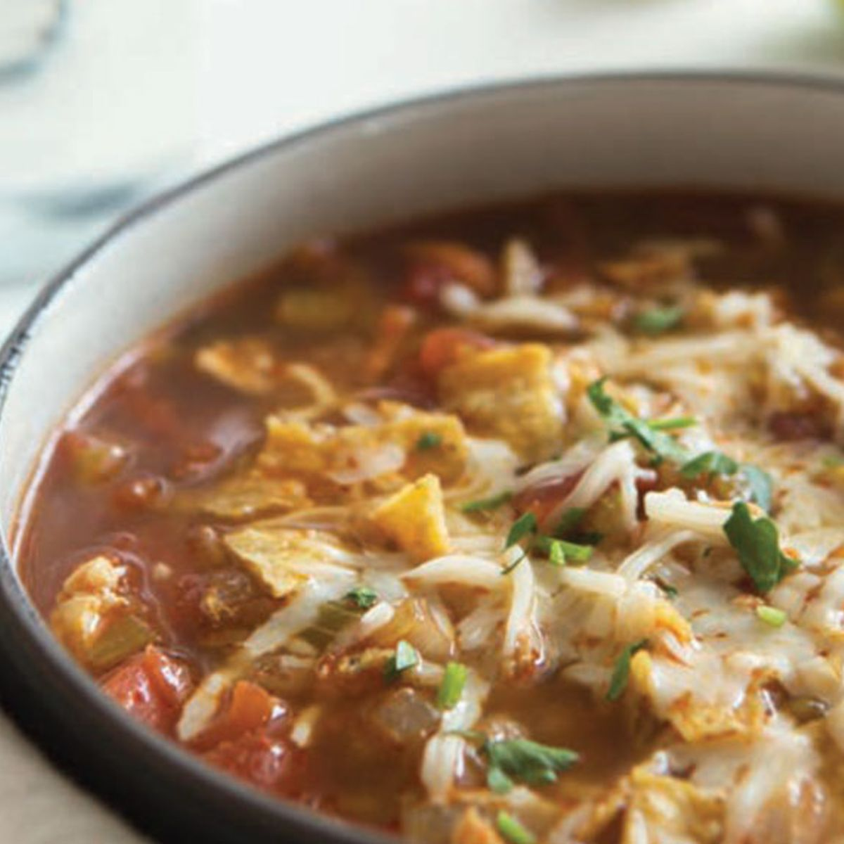 Top every serving of this chicken taco soup with broken tortilla chips and grated cheese