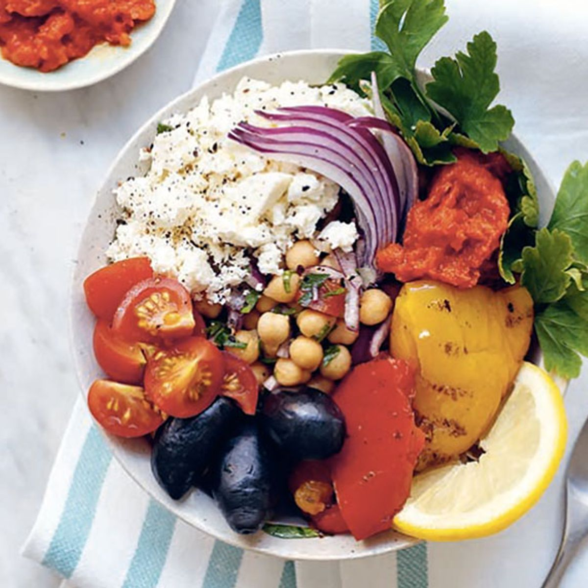 Garnish this Greek poke bowl with parsley, red onion and lemon slices