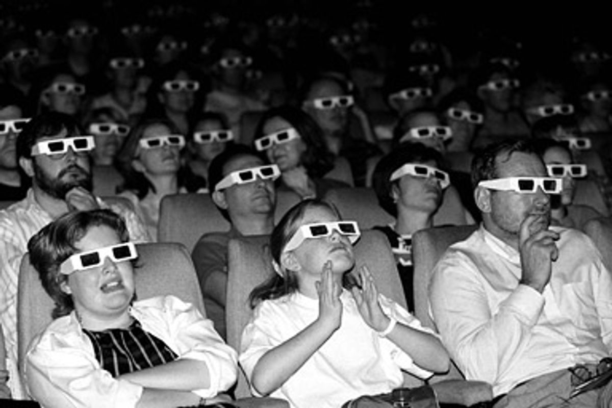 An audience watches a film through 3D glasses.