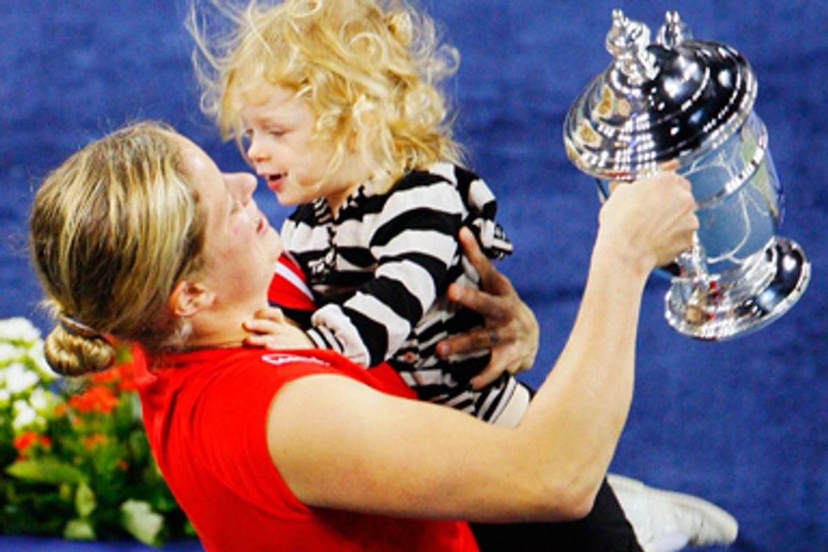 Kim Clijsters of Belgium carries her daughter Jada as she holds the trophy after defeating Caroline Wozniacki of Denmark in the women's singles final match at the U.S. Open tennis tournament in New York, September 13, 2009.