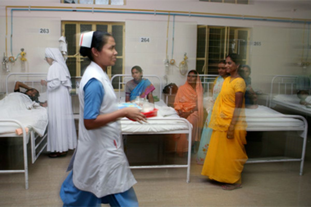 A nurse carries a tray to examine patients in an indoor ward at Nazareth Hospital in Allahabad, India, Sunday, May 11, 2008.