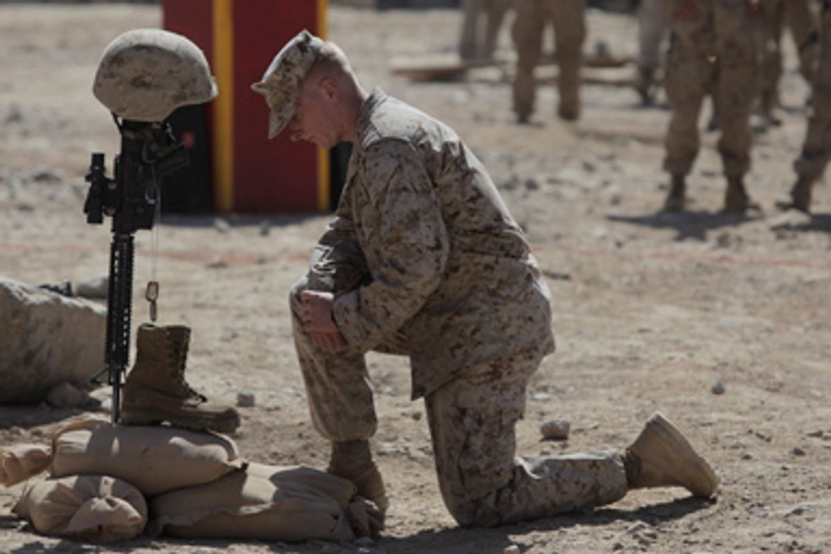 In this Thursday, Aug. 27, 2009 file photo, U.S. Marine Lt. Jake Godby pays his respects to Lance Cpl. Joshua Bernard during a memorial service at a forward operating base with Golf Company, 2nd Battalion, 3rd Marines, in Now Zad in the Helmand Province of Afghanistan.