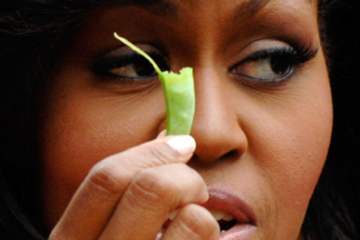 U.S. first lady Michelle Obama holds a bean harvested from vegetables grown in her garden at the White House in Washington June 16, 2009