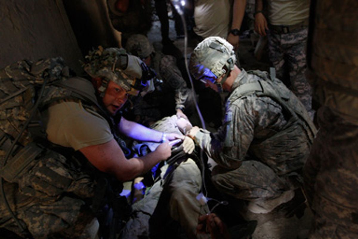 A wounded U.S. soldier receives first aid inside a bunker in the village of Bargematal, Nuristan province, August 25, 2009.