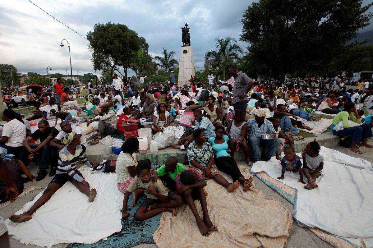 People sit at a park a day after the destructive earthquake in downtown Port-au-Prince, Wednesday, Jan. 13, 2010. The 7.0-magnitude earthquake that hit Haiti on Tuesday flattened the president's palace, the cathedral, hospitals, schools, the main prison and whole neighborhoods. (AP Photo/Gregory Bull)  (Associated Press)