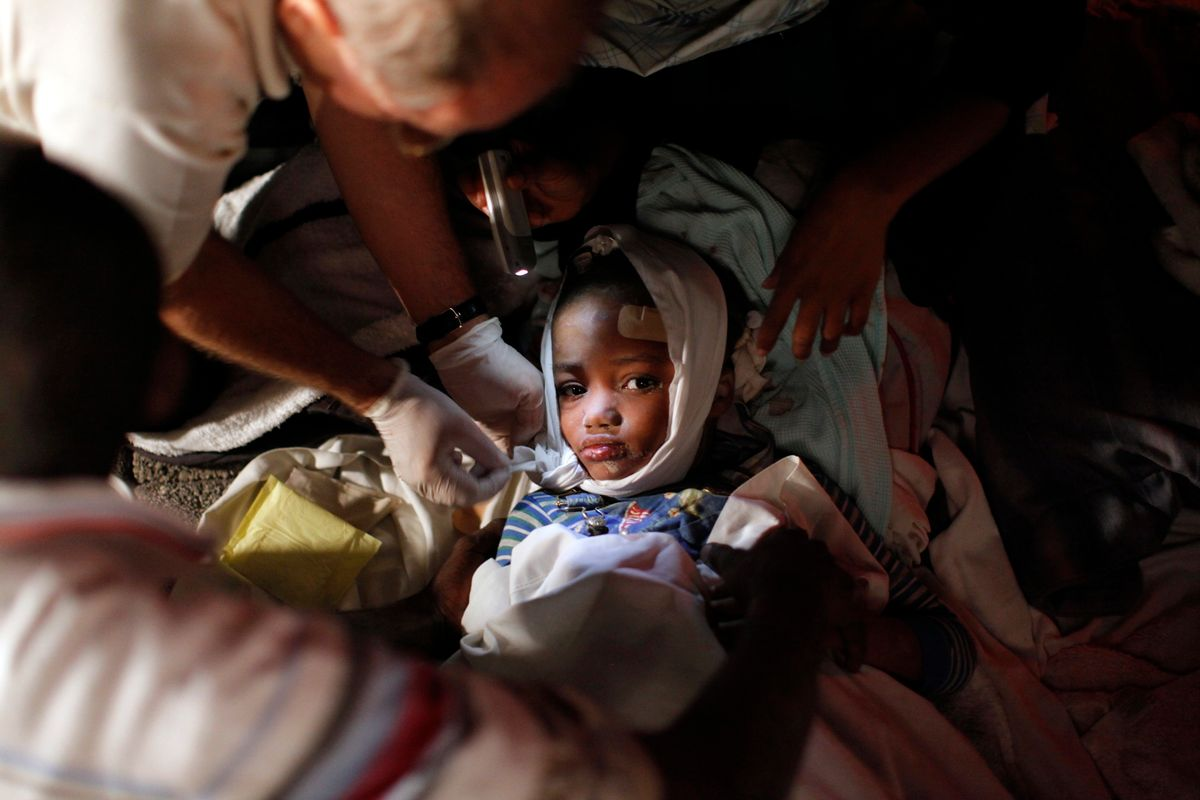 A injured child receives medical treatment after an earthquake in Port-au-Prince January 13, 2010. The  7.0 magnitude quake rocked Haiti, killing possibly thousands of people as it toppled the presidential palace and hillside shanties alike and leaving the poor Caribbean nation appealing for international help. REUTERS/Eduardo Munoz (HAITI tags: - Tags: DISASTER ENVIRONMENT IMAGES OF THE DAY) (Reuters)