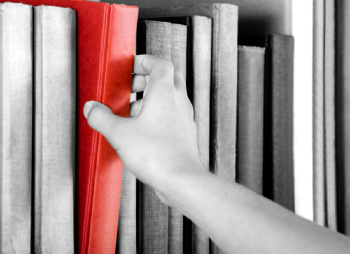 Image of a hand selecting a red book from a bookshelf (Andreas G. Karelias)