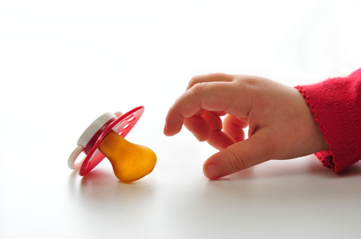Children's dummy. Child taking the pacifier.