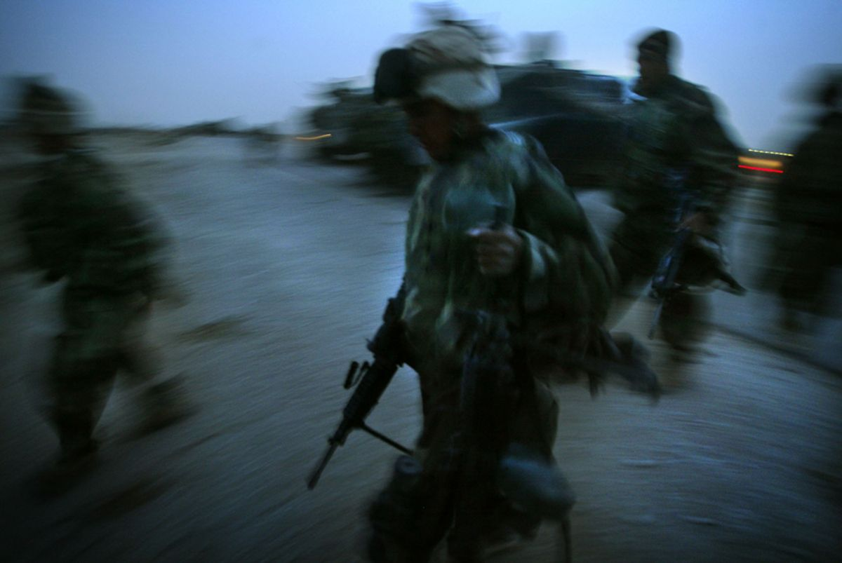 U.S. marines run with their combat gear to take position in the suburbs of the town of Nasariyah in Iraq March 24, 2003. U.S. marines were fighting on Monday to take control of Nassiriya where the city's defenders were putting up stout resistance. REUTERS/Damir Sagolj    Pictures of the month March 2003  DS/FMS   (© Reuters Photographer / Reuters)