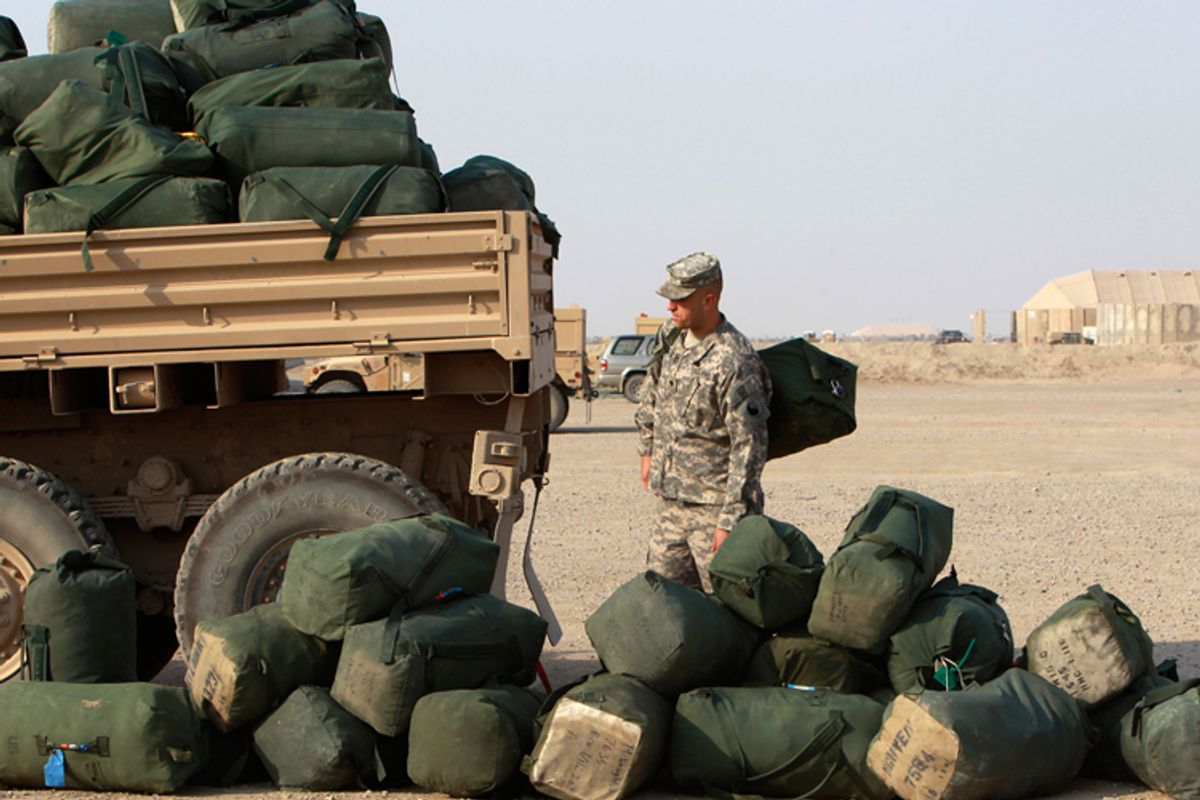 A U.S. soldier from the 1st Battalion, 116th Infantry Regiment, waits to load his bag onto a military vehicle carrying other bags as he prepares to leave for Kuwait from Tallil Air Base near Nassiriya, Iraq, on August 15.