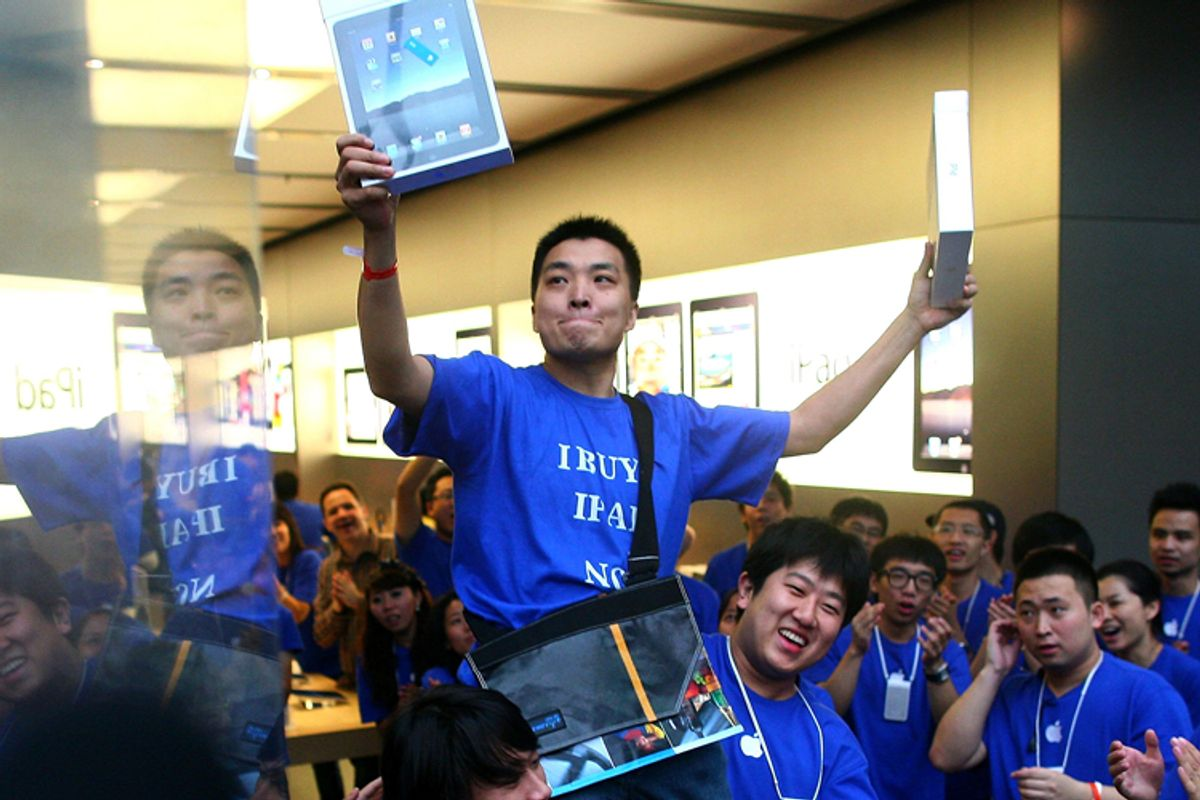 Customer Han Ziwen holds up his iPads while being carried out by store employees at the Apple flagship store in Beijing
