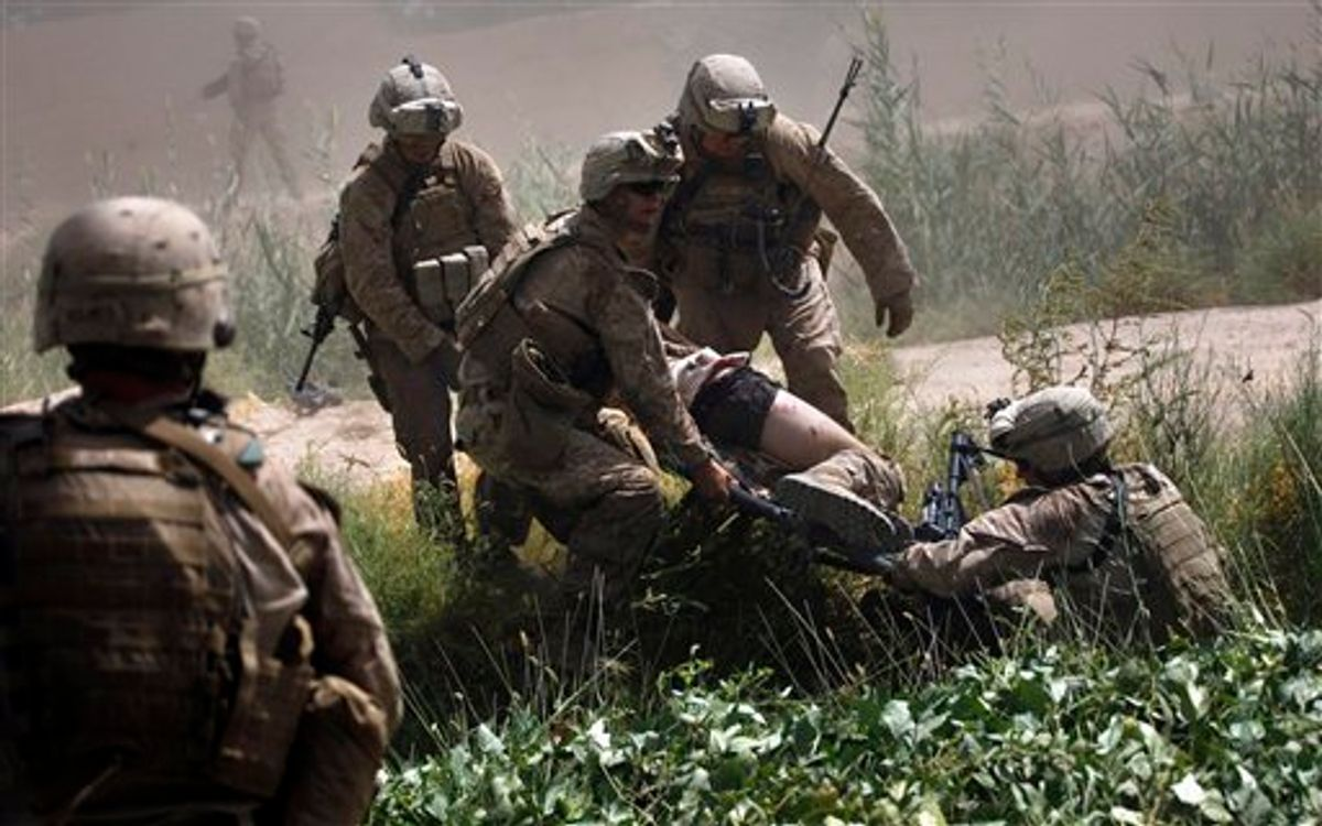 U.S. Marines prepare to carry one of two comrades wounded in an IED attack to a waiting U.S. Army Task Force Shadow medevac helicopter on a rescue mission west of Lashkar Gah, in southern Afghanistan, Saturday, Sept. 4, 2010. Aeromedical teams with the 101st Airborne's Task Force Destiny provide the fast medical evacuation of those wounded throughout southern Afghanistan. (AP Photo/Brennan Linsley) (AP)