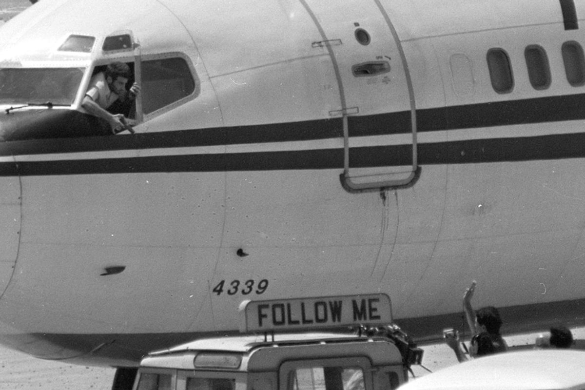 A hijacker points his pistol from the cockpit of TWA Flight 847 as an ABC news crew approaches the jet for an interview at Beirut International Airport on June 19, 1985.