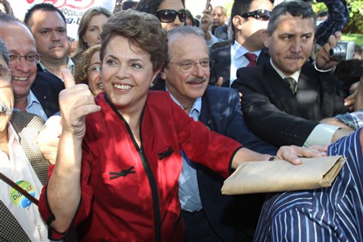 Dilma Rousseff, presidential candidate for the governing Workers Party, greets supporters as he leaves a polling station after voting in Brazil's presidential election runoff in Porto Alegre, Brazil, Sunday Oct. 31, 2010.  (AP Photo/Nabor Goulart) (AP)