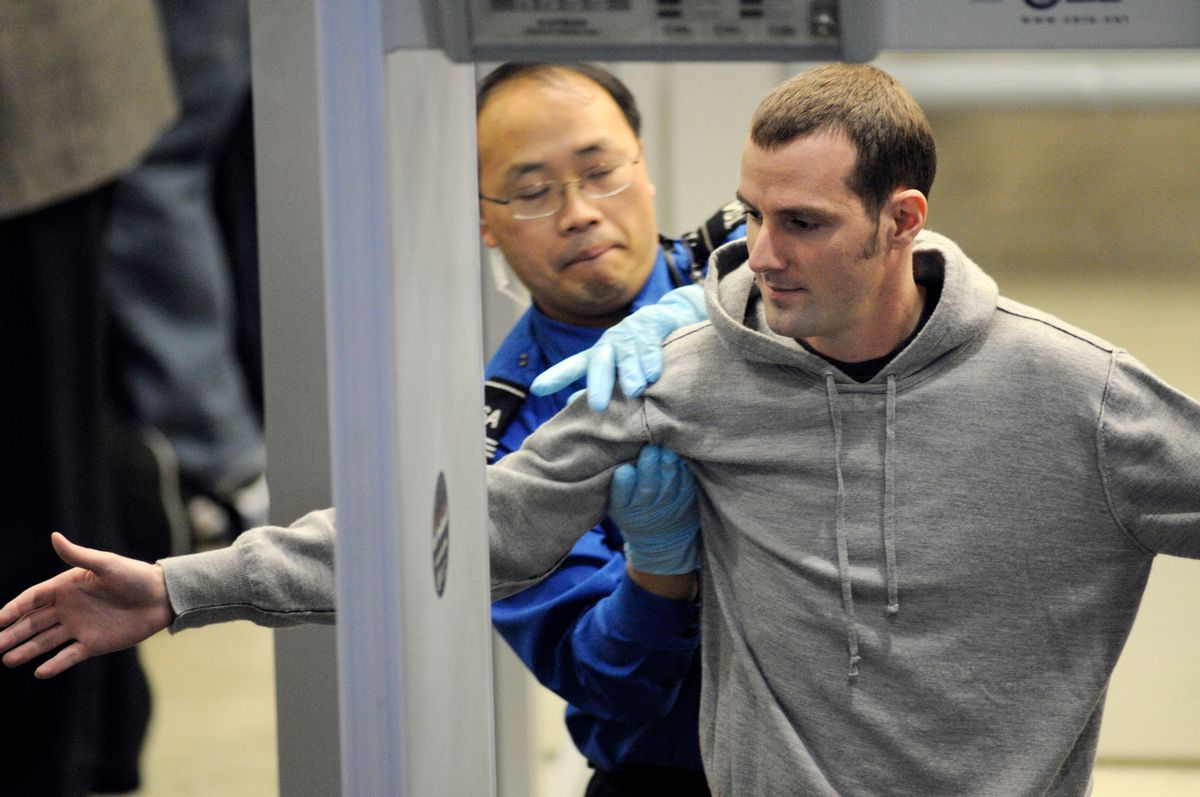 Transportation Security Administration (TSA) officer pats down a traveler as he works his way through security at the Minneapolis-St. Paul International Airport in Bloomington, Minn., Wednesday, Nov. 24, 2010.  (AP Photo/Craig Lassig)