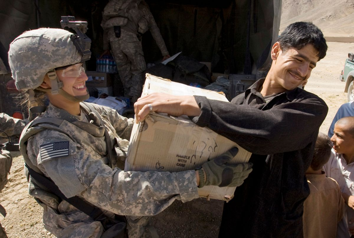 U.S. Private Charlie Johnson of 3rd Brigade Special Troops Battalion, 10th Mountain Division gives a box to an Afghan man during a hospital supply delivery in the village of Dah-e-Naw in Logar Province of Afghanistan July 23, 2009.   REUTERS/Shamil Zhumatov (AFGHANISTAN CONFLICT MILITARY POLITICS SOCIETY)  (?? Shamil Zhumatov / Reuters)