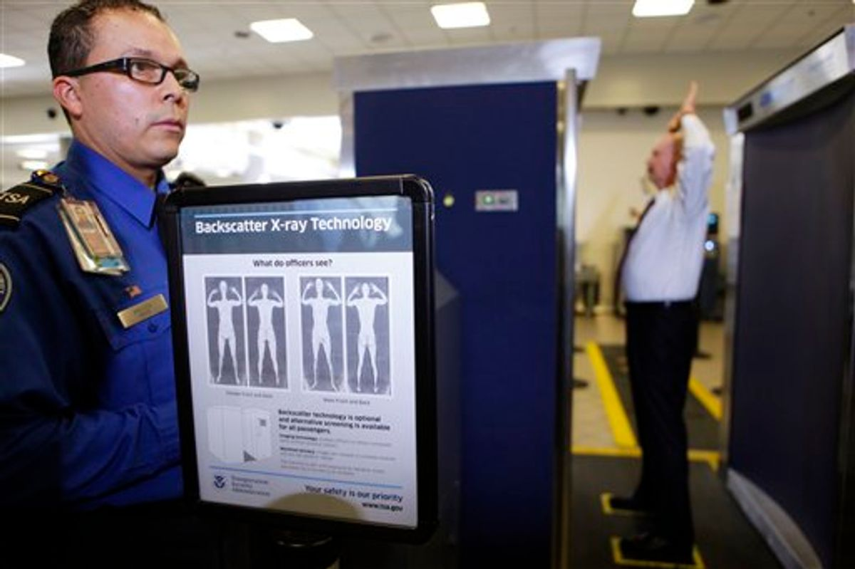 Transportation Security Administration screener Marlon Tejada, left, watches as Randy Parsons, TSA acting Federal Security Director, right, goes through a full body X-ray scanner for a security screening Monday, Nov. 22, 2010, at the Los Angeles International airport. (AP Photo/Damian Dovarganes) (AP)