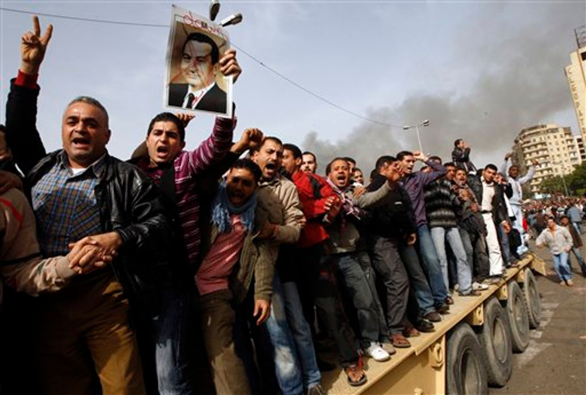 Egyptian anti-government activists, one of them holding a crossed-out portrait of Egyptian President Hosni Mubarak, chant slogans as they protest in downtown Cairo, Egypt, Saturday, Jan. 29, 2011. (AP Photo/Khalil Hamra) (AP)