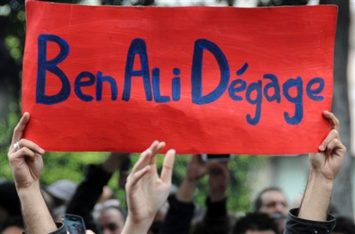 """Protestors hold a banner reading """"Ben Ali get out"""", calling for the resignation of Tunisia's President Zine El Abidine Ben Ali, in the capital, Tunis, Friday, Jan. 14,2011. Thousands of angry demonstrators marched through Tunisia's capital Friday, demanding the resignation of the country's autocratic leader a day after he appeared on TV to try to stop deadly riots that have swept the North African nation. (AP Photo) (AP)"""