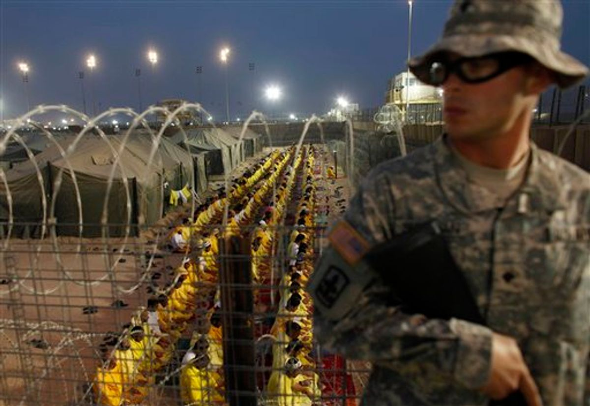 FILE - In this March 16, 2009 file photo, a U.S. soldier stands guard as detainees pray at U.S. military detention facility Camp Bucca, Iraq. A former prison camp that was run by the U.S. military in southern Iraq will be turned into a commercial center with offices, warehouses, aviation and fuel services that will support country's investment activities, an Iraqi official said Monday, Dec. 20, 2010. (AP Photo/Dusan Vranic, File) (AP)