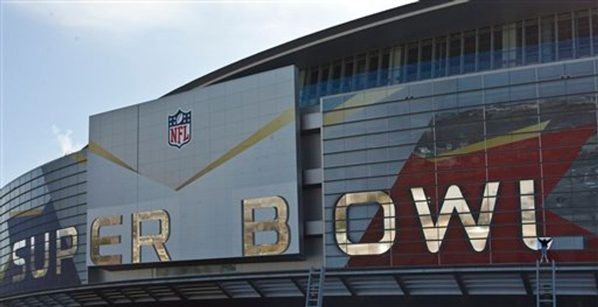 A worker puts up a logo outside Cowboys Stadium, Tuesday, Jan. 25, 2011 in Arlington, Texas, in preparation of NFL football Super Bowl XLIV. (AP Photo/Morry Gash) (AP)