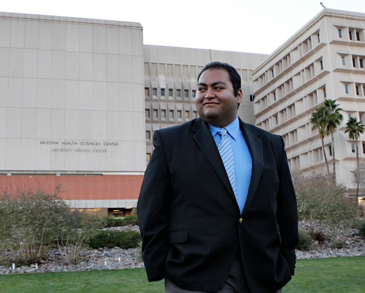 Daniel Hernandez, an intern with U.S. Rep. Gabrielle Giffords, D-Ariz., walks across the lawn outside University Hospital Sunday, Jan. 9, 2011 in Tucson, Ariz. Hernandez attended to Giffords and others immediately after Giffords was shot in the head a day earlier during a speech at a local supermarket. (AP Photo/Matt York) (AP)