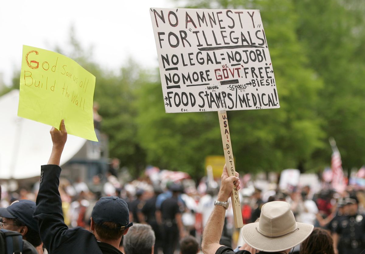 Anti-immigration demonstrators hold signs at an immigration rally in Dallas on Saturday, May 1, 2010. Large crowds were expected in Dallas after a new Arizona law passed requiring authorities to question people about their immigration status if they are suspected of being in the country illegally. (AP Photo/Mike Fuentes) (Associated Press)