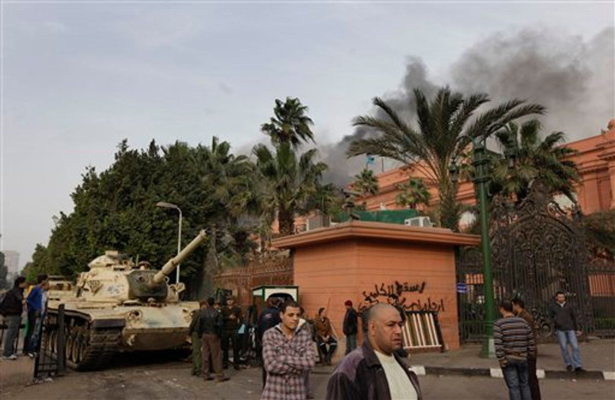 An Egyptian army tank stands outside the Egyptian museum which remains intact,  right, as smoke billows in the background from the ruling National Democratic party building, torched by anti government protesters overnight, in central Cairo, Egypt, Saturday, Jan. 29, 2011. (AP Photo/Ben Curtis) (AP)