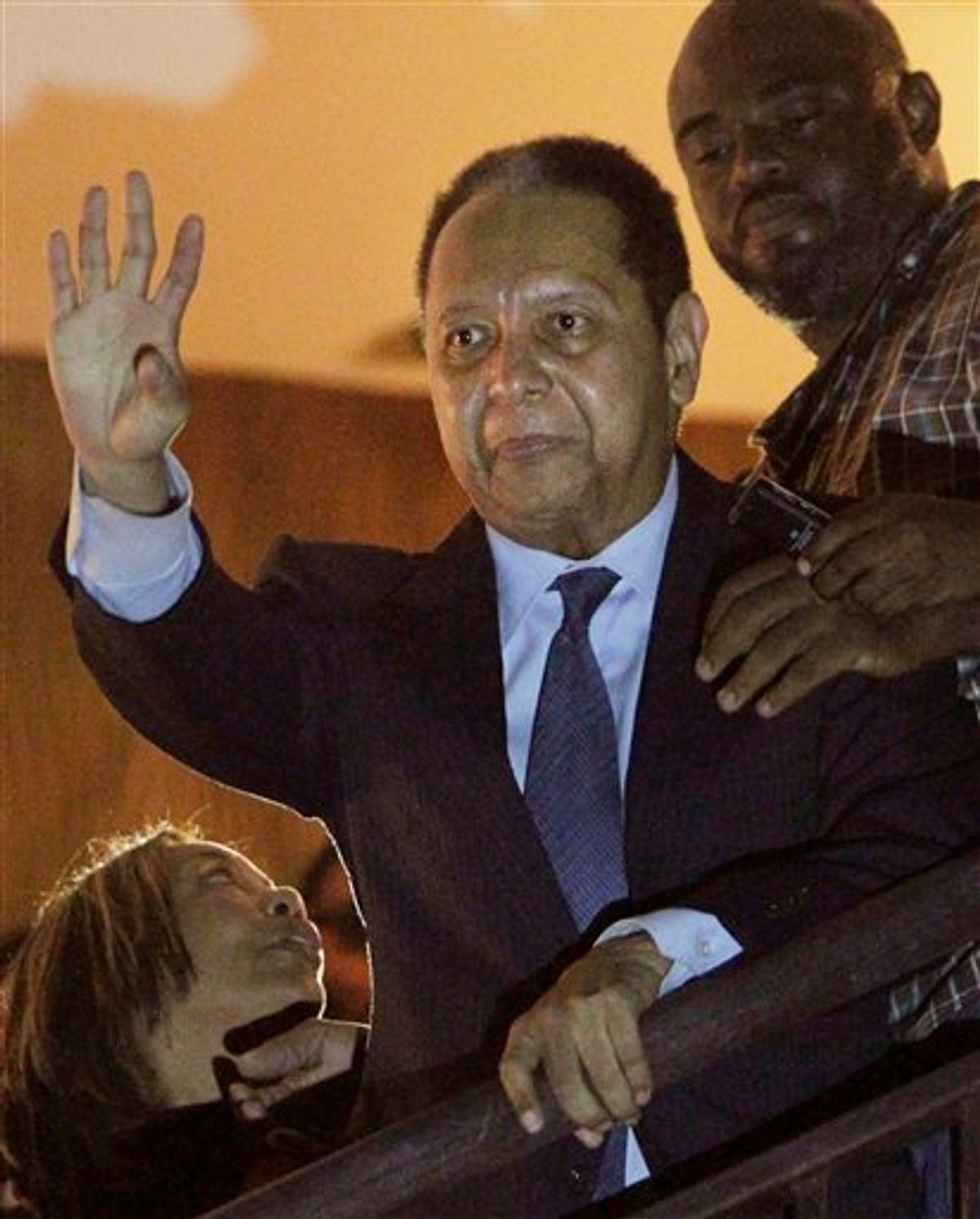 """ALTERNATIVE CROP OF PAP109 - Haiti's former dictator Jean-Claude """"Baby Doc"""" Duvalier, center, waves to supporters from a hotel balcony after his arrival in Port-au-Prince, Haiti, Sunday Jan. 16, 2011. Duvalier returned Sunday to Haiti after nearly 25 years in exile, a surprising and perplexing move that comes as his country struggles with a political crisis and the stalled effort to recover from last year's devastating earthquake. (AP Photo/Dieu Nalio Chery) (AP)"""