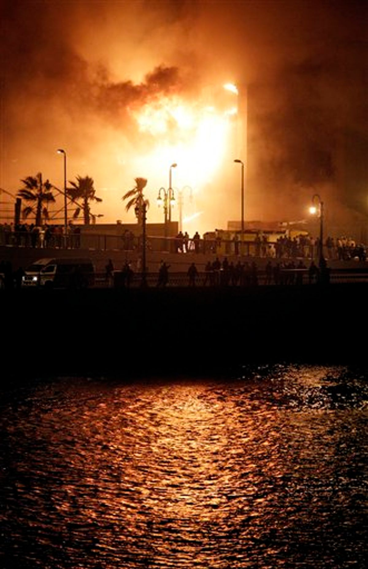 Fires burn in the National Democratic Party ruling party headquarters, after it was set alight by anti-government protesters, in downtown Cairo, Egypt, Friday, Jan. 28, 2011. (AP Photo/Ben Curtis) (AP)