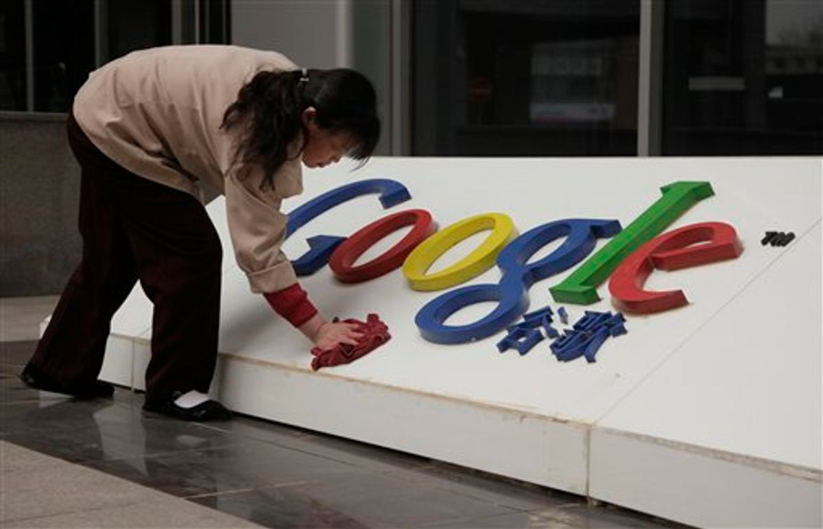 In this photo taken Monday, March 22, 2010, a Chinese woman cleans the Google logo outside the Google China headquarters in Beijing, China.  A leaked U.S. government cable shows sources told American diplomats that hacking attacks against Google were ordered by China's top ruling body.  (AP Photo/Ng Han Guan) (AP)