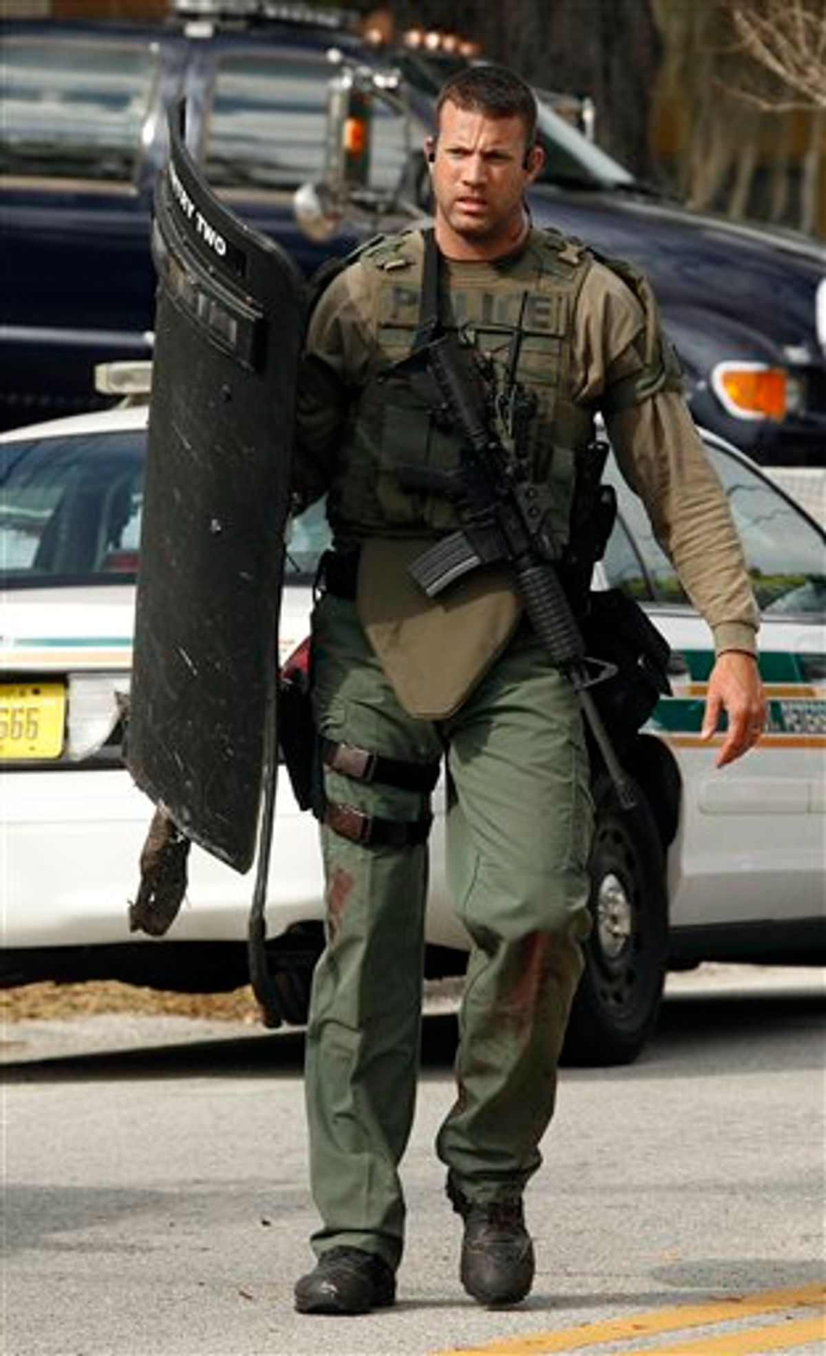 A heavily armed SWAT team member walks away from the scene where three officers were shot Monday, Jan. 24, 2011 in south St. Petersburg, Fla.  Police say a gunman suspected of killing two Florida police officers and wounding a U.S. marshal during a shootout has been found dead. St. Petersburg Police spokesman Michael Puetz says the suspect was found dead when officers went into the home Monday afternoon, about six hours after the shootout. Puetz said officers originally went to the home to arrest 39-year-old Hydra Lacy Jr.  (AP Photo/Chris O'Meara) (AP)