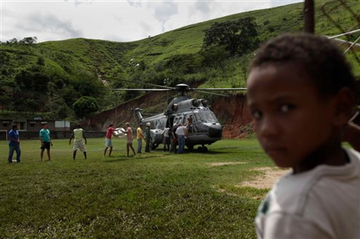 A boy looks on as residents unload supplies from an Navy helicopter at Sumidouro, an area isolated due to landslides in Teresopolis, Brazil, Tuesday, Jan. 18, 2011. Brazil's army on Monday sent some 700 soldiers to help throw a lifeline to desperate neighborhoods that have been cut off from food, water or help in recovering bodies since mudslides killed at least 665 people. (AP Photo/Felipe Dana) (AP)