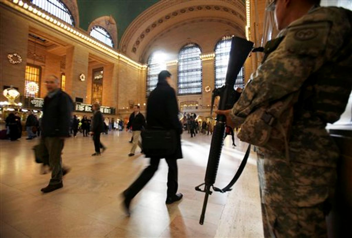 FILE - In this Nov. 24, 2010 file photo, National Guard security personnel watch as travelers make their way through Grand Central Station in New York. As the holiday tourist season begins in the Big Apple, there are reminders everywhere of how being the country's main target for terrorism has gradually changed this city. (AP Photo/Seth Wenig, File) (AP)