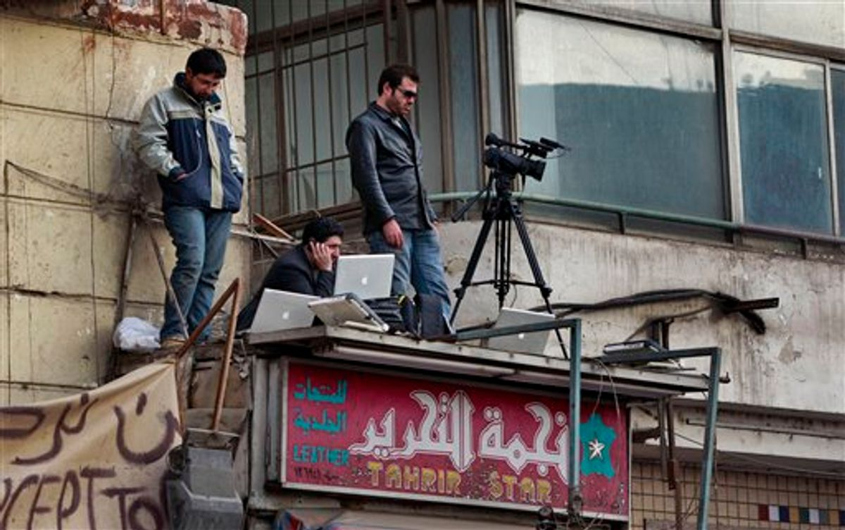 """A television cameraman and colleagues standing on the awning of a shop transmit footage by satellite-phone of the continuing protest in Tahrir Square in downtown Cairo, Egypt Monday, Feb. 7, 2011. Egypt's embattled regime announced Monday a 15 percent raise for government employees in an attempt to shore up its base and defuse popular anger but the gestures so far have done little to persuade the tens of thousands of protesters occupying Tahrir Square to end their two-week long protest, leaving the two sides in an uneasy stalemate. Name of shop on sign in arabic reads """"Tahrir Star Leather"""". (AP Photo/Ben Curtis) (AP)"""