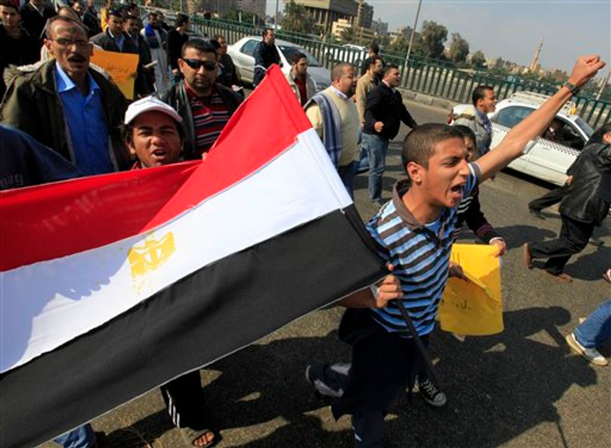 Anti-government protesters wave an Egyptian flag during a march in Cairo, Egypt, Friday, Feb. 11, 2011. Egypt's powerful military backed President Hosni Mubarak's plan to stay in office until September elections, but massive crowds outraged by his refusal to step down packed squares in Egypt's two biggest cities Cairo and Alexandria on Friday. (AP Photo/Amr Nabil) (AP)