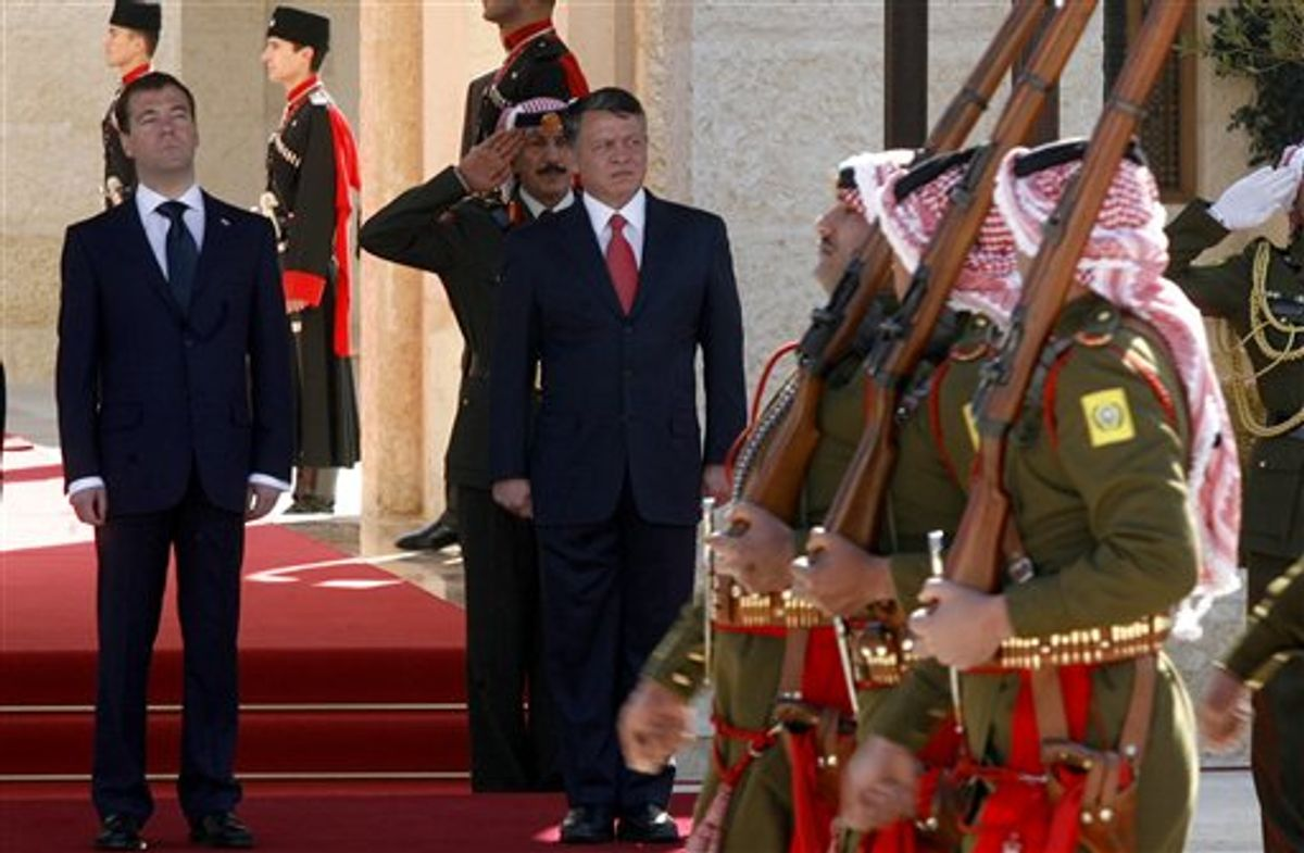 King Abdullah II of Jordan, center, and Russian President Dmitry Medvedev, left, review the Bedouin guards of honor during an official welcoming ceremony prior their talks, in Amman, Jordan, Wednesday, Jan. 19, 2011. (AP Photo/Nader Daoud)  (AP)
