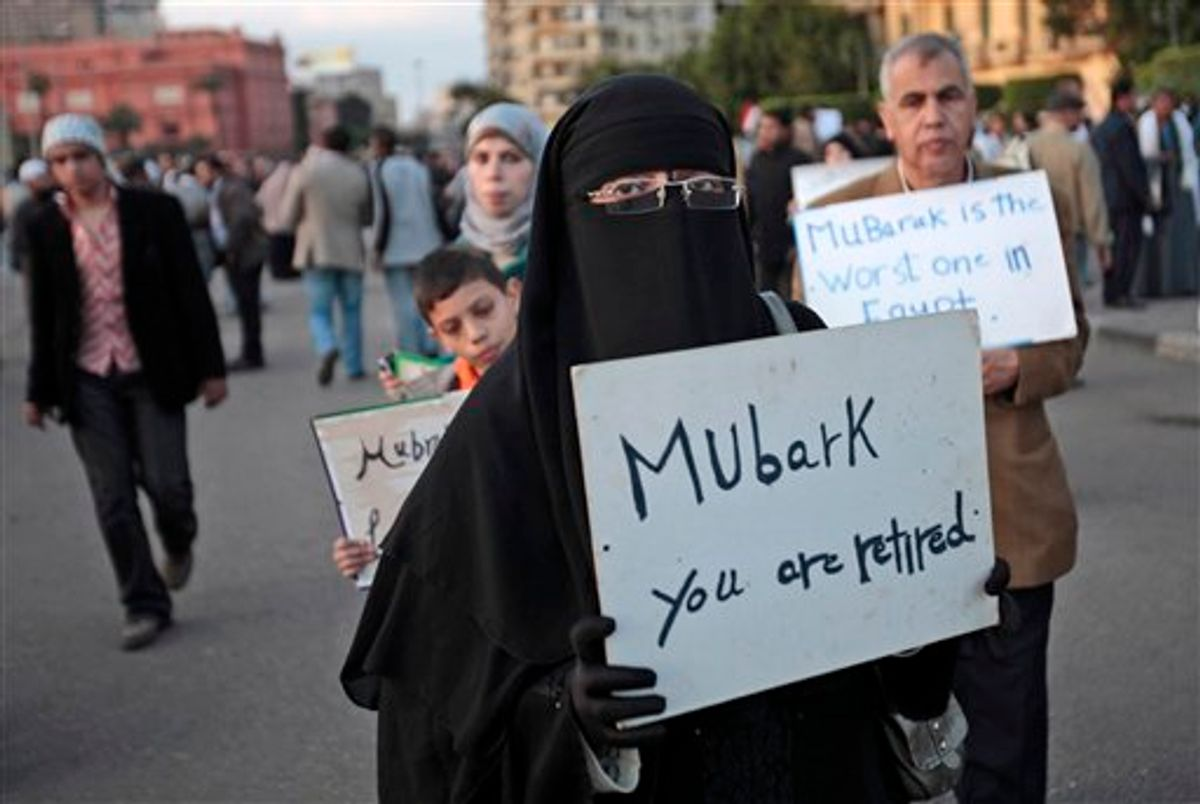 A woman carrying a placard referring to Egyptian President Hosni Mubarak attends a demonstration by anti-government protesters in Cairo's Tahrir Square, Egypt, Monday, Jan. 31, 2011. A coalition of opposition groups called for a million people to take to Cairo's streets Tuesday to demand the removal of Mubarak. AP Photo/Lefteris Pitarakis) (AP)
