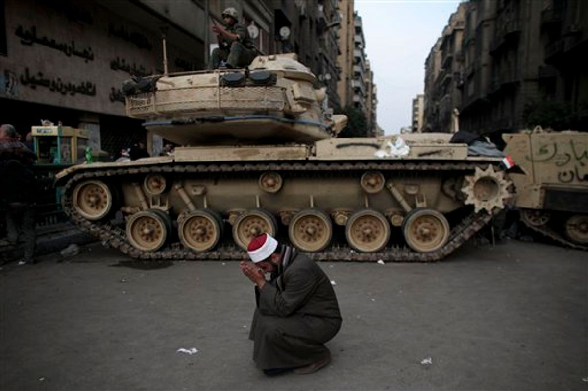 An Egyptian Muslim cleric cries in front of on army tank in Tahrir, or Liberation square, in Cairo, Egypt, Wednesday, Feb. 2, 2011. Several thousand supporters of President Hosni Mubarak, including some riding horses and camels and wielding whips, clashed with anti-government protesters Wednesday as Egypt's upheaval took a dangerous new turn. (AP Photo/Tara Todras-Whitehill) (AP)