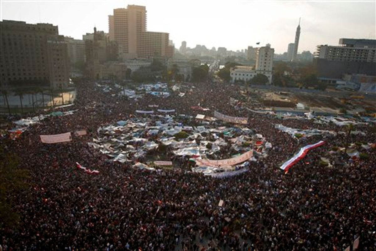"""Anti-government protesters demonstrate in Tahrir Square, in Cairo, Egypt, Tuesday, Feb. 8, 2011. Protesters appear to have settled in for a long standoff, turning Tahrir Square into a makeshift village with tens of thousands coming every day, with some sleeping in tents made of blankets and plastic sheeting. The arabic on the sign reads """"The rage brings the light of freedom"""". (AP Photo/Tara Todras-Whitehill) (AP)"""