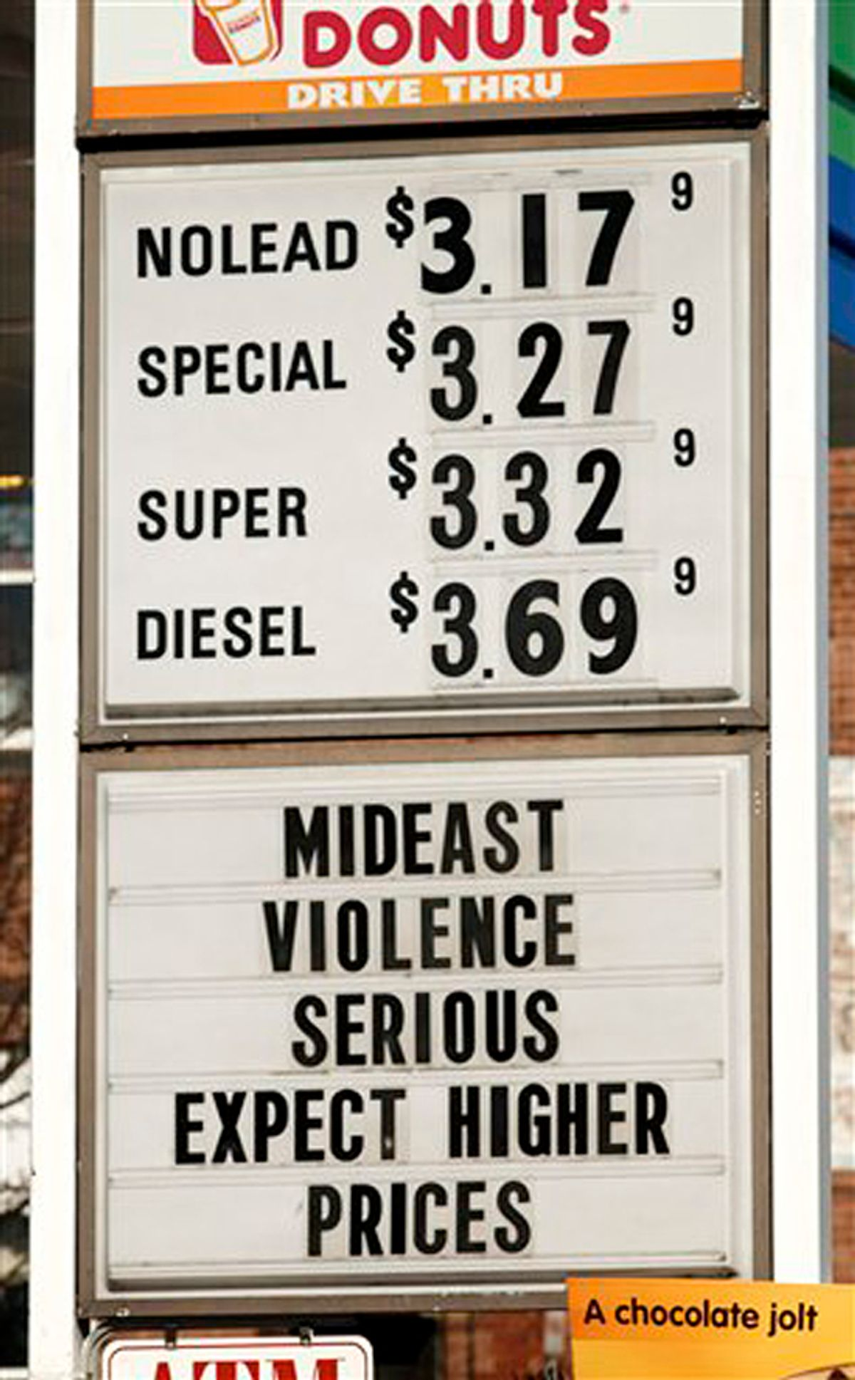 A sign advertises gas and diesel prices, plus gives an explanation to customers, at a service station in Easthampton, Mass, Wednesday, Feb. 23, 2011. Oil prices rose past $99 a barrel on Wednesday as forces loyal to Libya's Moammar Gadhafi clashed with protesters expanding their control over parts of the country. (AP Photo/ Shana Sureck)  (Shana Sureck)