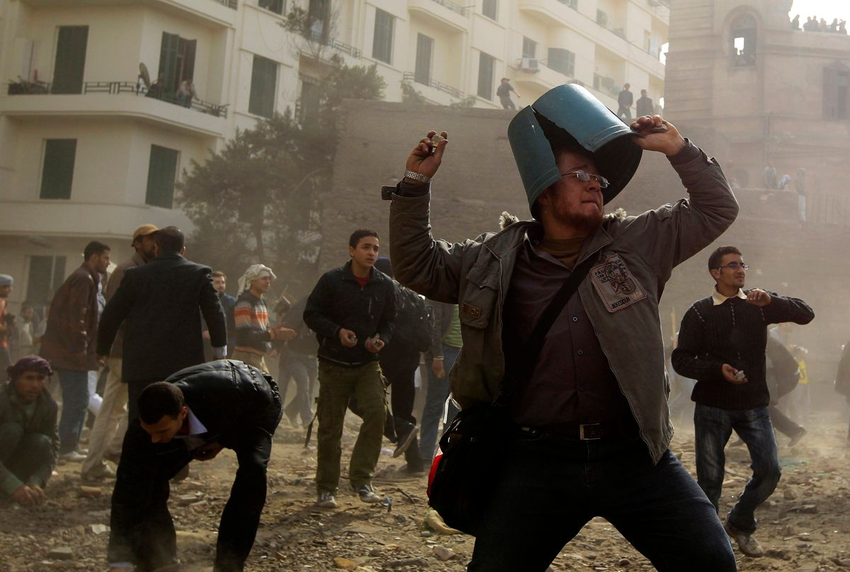An opposition demonstrator throws a rock during rioting with pro-Mubarak supporters near Tahrir Square in Cairo February 3, 2011. Anti-government protesters and supporters of Mubarak clashed on Thursday near a central Cairo square in a re-run of overnight violence that killed six and wounded more than 800 people.  REUTERS/Goran Tomasevic (EGYPT - Tags: POLITICS CIVIL UNREST)     (© Goran Tomasevic / Reuters)