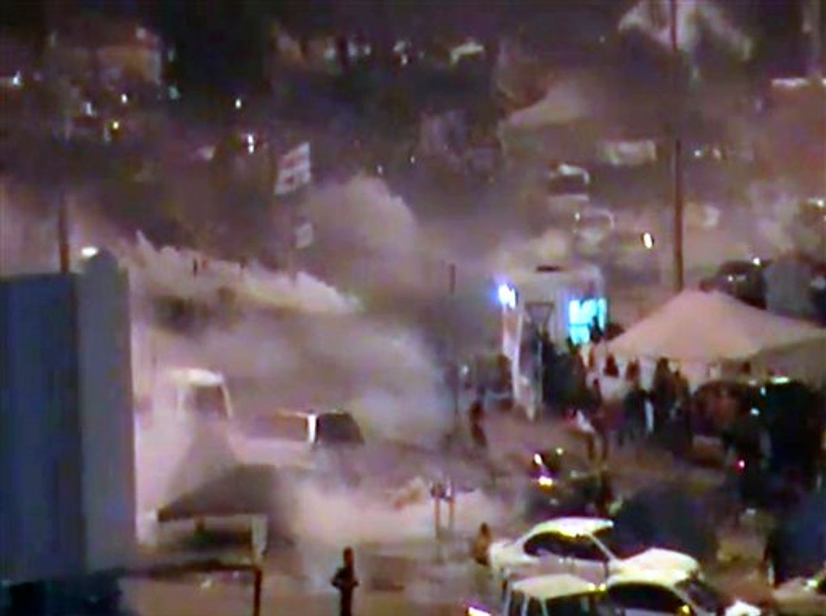 In this image from video riot police firing tear gas and wielding clubs storm Pearl Square occupied by anti-government protesters before dawn Thursday, Feb. 17, 2011 driving out demonstrators and destroying a makeshift encampment that had become the hub for demands to bring sweeping political changes to the kingdom. (AP Photo/Tony Mitchell, HO) (AP)