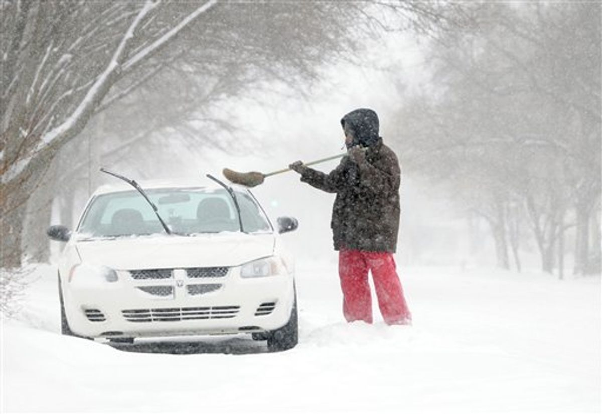 """Marques Lewis sweeps snow from his car, Tuesday, Feb. 8, 2011, in Salina, Kan. Lewis said he was """"getting ready to go to work"""" and had to """"start a little early."""" Three to four inches had fallen in the Salina area by mid-morning with the temperature at five degrees. (AP Photo/Salina Journal, Tom Dorsey) (AP)"""