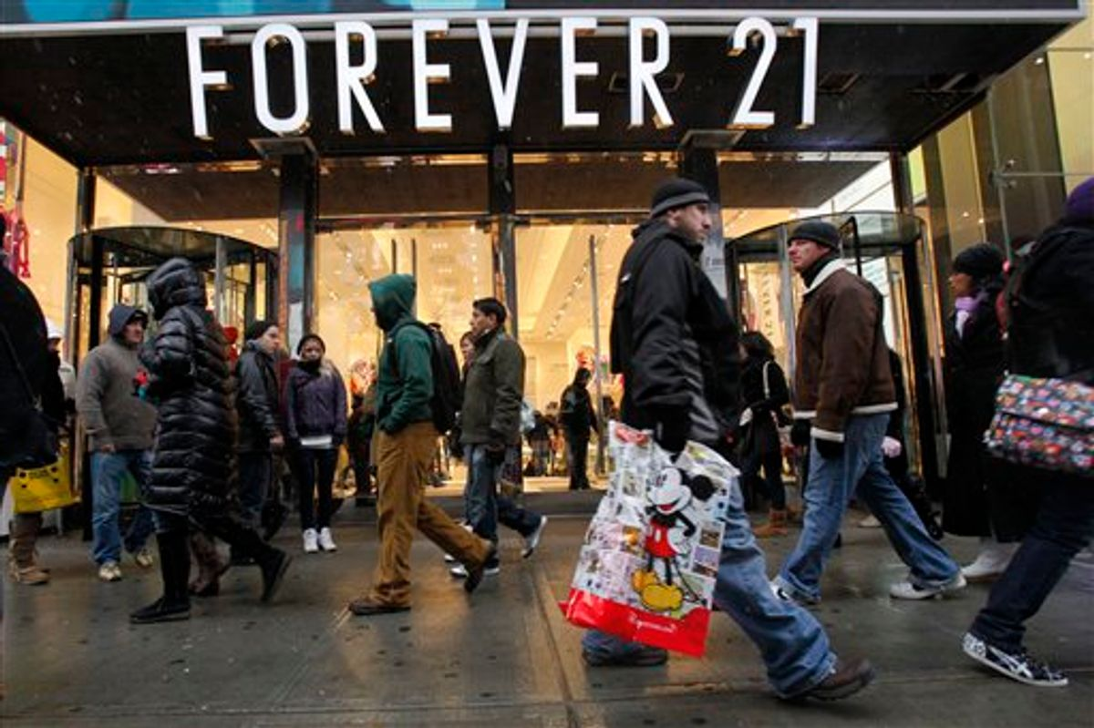 FILE - In this Dec. 26, 2010 file photo, people walk past a Forever 21 store in New York's Times Square. The population of the U.S. has grown by 8 million people since the previous record was set. That means there were millions more shoppers in stores this Christmas, driving up the sales total. But the average amount of spending per person was down from a few years ago, suggesting consumers are still slower to pull out their wallets. (AP Photo/Mary Altaffer, file) (AP)