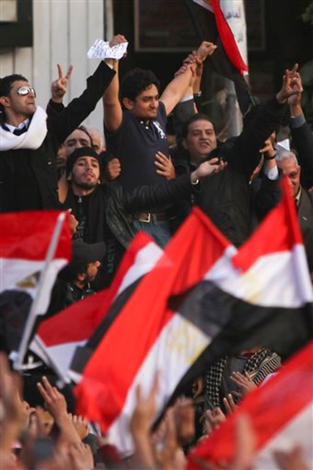 """Egyptian Wael Ghonim, center, a 30-year-old Google Inc. marketing manager who was a key organizer of the online campaign that sparked the first protest on Jan. 25, gestures to the crowd in Tahrir Square, in Cairo, Egypt, Tuesday, Feb. 8, 2011. A young leader of Egypt's anti-government protesters, newly released from detention, joined a massive crowd of hundreds of thousands in Cairo's Tahrir Square for the first time Tuesday, greeted by cheers, whistling and thunderous applause when he declared: """"We will not abandon our demand and that is the departure of the regime."""" (AP Photo/Tara Todras-Whitehill) (AP)"""