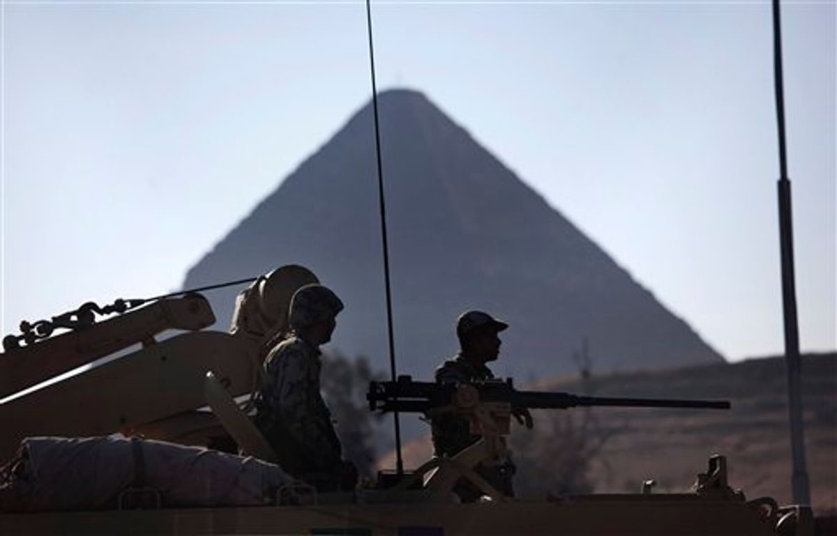 Egyptian Army soldiers are seen on top of an APC vehicle near the pyramids, in Giza, Egypt, Monday, Jan. 31, 2011. The pyramids are closed to tourists.  A coalition of opposition groups called for a million people to take to Cairo's streets Tuesday to demand the removal of President Hosni Mubarak (AP Photo/Emilio Morenatti) (AP)