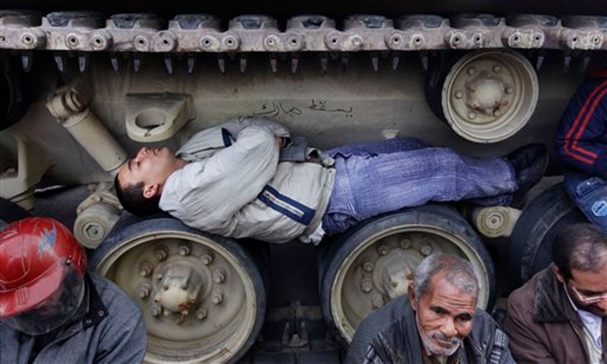Anti-government protesters sit and lie inside the tracks of an Egyptian Army tank, both to prevent them from moving and to shield themselves from the rain, at the protest site opposite the Egyptian Museum near Tahrir Square in downtown Cairo, Egypt Sunday, Feb. 6, 2011. Egypt's vice president met a broad representation of major opposition groups for the first time Sunday and agreed to allow freedom of the press and to release those detained since anti-government protests began, though Al-Jazeera's English-language news network said one of its correspondents had been detained the same day by the Egyptian military. (AP Photo/Ben Curtis) (AP)