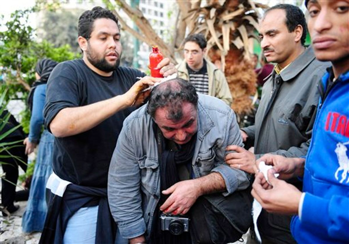 French photojournalist from SIPA Press agency Alfred Yaghobzadeh is being treated by anti-government protestors after being wounded during clashes between pro-government supporters and anti-government protestors, in Cairo's central Tahrir Square, Wednesday Feb. 2, 2011 in Cairo, Egypt.  The Egyptian military has started Thursday Feb.3, 2011 rounding up journalists, possibly for their own protection, after they came under attack from supporters of President Hosni Mubarak who have been attacking anti-government protesters. (AP Photo) (AP)