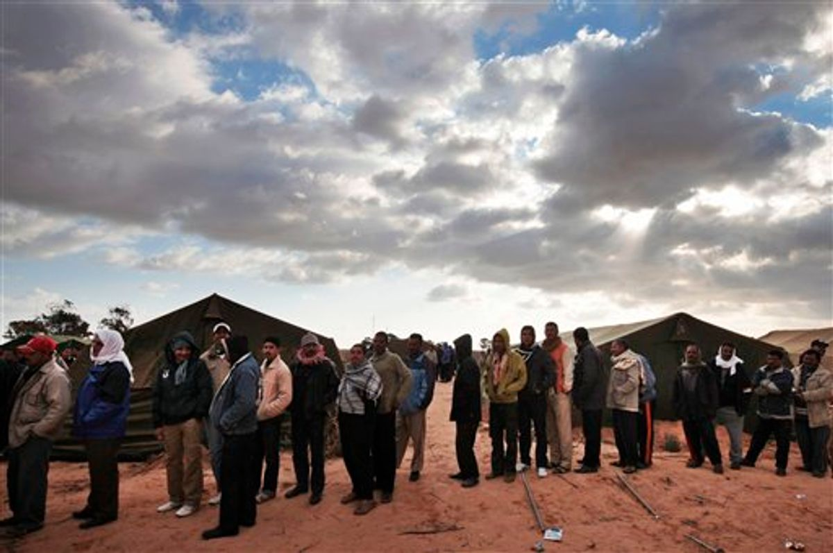 Egyptians, who used to work in Libya, and fled the unrest in the country, wait for their breakfast in a makeshift refugee camp set up by the Tunisian army, at  the Tunisia-Libyan border, in Ras Ajdir, Tunisia,  Friday, Feb. 25, 2011. (AP Photo/Lefteris Pitarakis)  (AP)